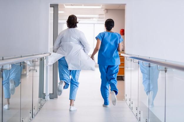 Verpleegster en arts die in het ziekenhuisgang lopen