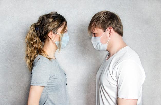 Verpleegster en arts in steriele uniformen en maskers staan met gestrekte armen en kijken elkaar aan.