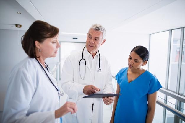Verpleegster en artsen die over digitale tablet bespreken