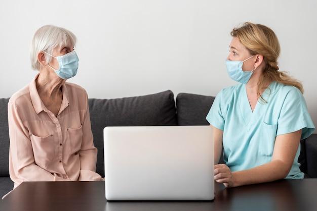 Verpleegster en oudere vrouw die bij het verpleeghuis praten