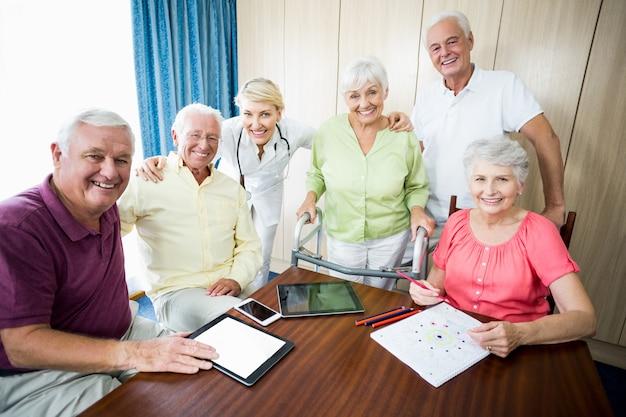 Verpleegster en senioren staan samen