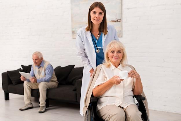 Verpleegster en vrouw die de camera bekijken