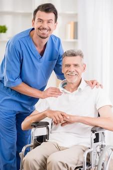 Verpleegster en zijn hogere patiënt in rolstoel bij het ziekenhuis.