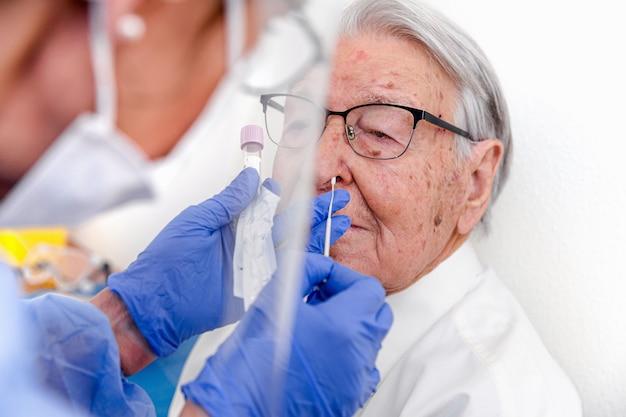 Verpleegster gekleed in beschermend pak en masker voor coronavirus, voert een coronavirus-test uit op oudere man.
