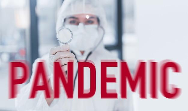 Verpleegster in beschermende uniform, masker en bril permanent binnenshuis