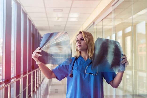 Verpleegster in blauw uniform controleert op longontsteking in de röntgenfilm van de longen. covid19