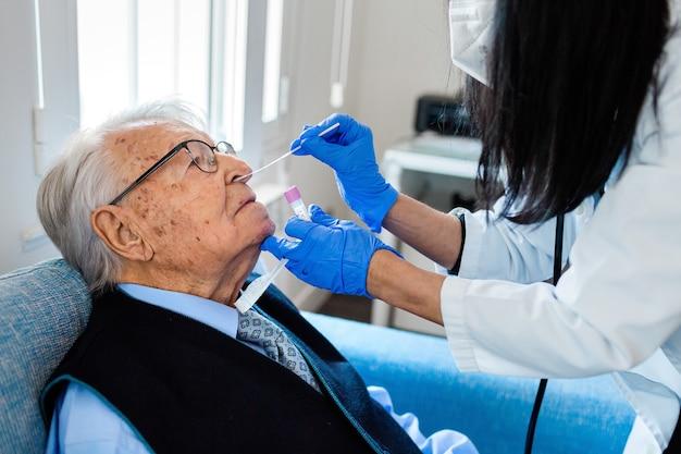 Verpleegster in blauwe sanitaire handschoenen tilt het hoofd van een oudere man in blauw overhemd en stropdas op om de covid-test uit te voeren terwijl hij thuis op de bank zit. thuiszorg.