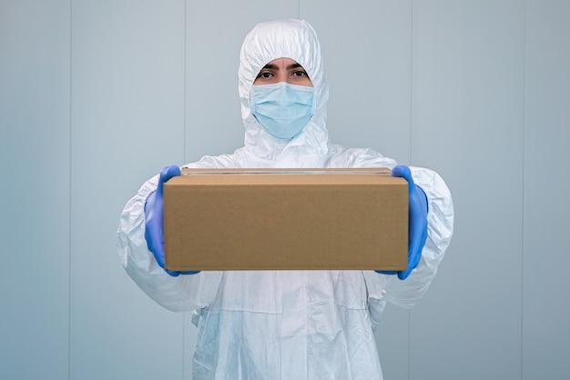 Verpleegster in een beschermend pak toont een doos met beide handen in een ziekenhuis