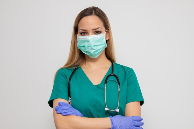 Verpleegster in groene kleding met medische masker en handschoenen