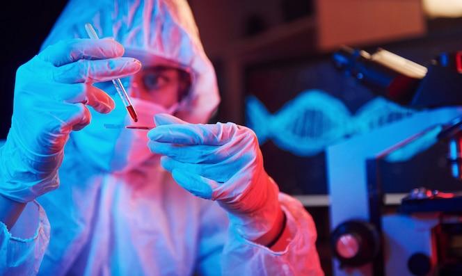 Verpleegster in masker en wit uniform, met buis met vloeistof en zittend in neonverlichte laboratorium met computer en medische apparatuur op zoek naar coronavirus vaccin