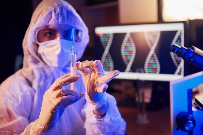 Verpleegster in masker en wit uniform, met spuit en zittend in neonverlichte laboratorium met computer en medische apparatuur op zoek naar coronavirus vaccin