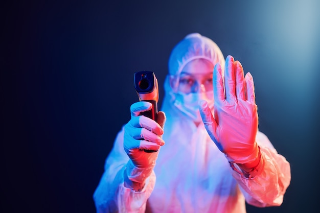 Verpleegster in masker en witte uniform staande in neon verlichte kamer en infrarood thermometer te houden. stop de verspreiding van het coronavirus