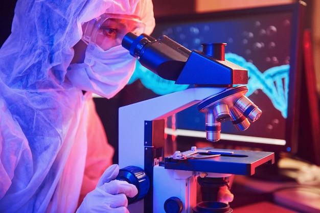 Verpleegster in masker en witte uniform zitten in neon verlichte laboratorium met computer, microscoop en medische apparatuur op zoek naar coronavirus vaccin