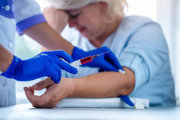Verpleegster in rubber blauwe medische handschoenen neemt bloedmonster uit een ader voor laboratoriumtest. medische onderzoek