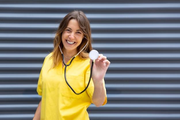 Verpleegster in uniform met behulp van een stethoscoop