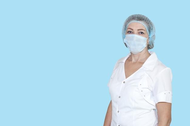 Verpleegster in witte jas met pet en masker