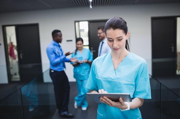 Verpleegster met behulp van digitale tablet in ziekenhuisgang