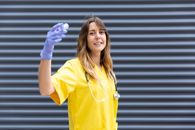 Verpleegster met beschermende handschoenen en een spuit in haar handen.