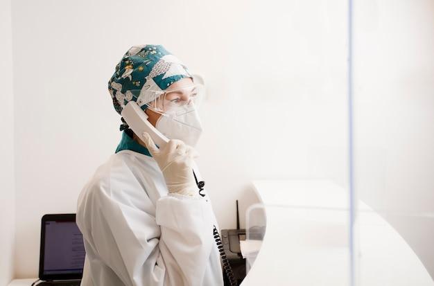 Verpleegster met persoonlijke beschermingsmiddelen en telefoon in handen, tandheelkundige ziekenhuisreceptie