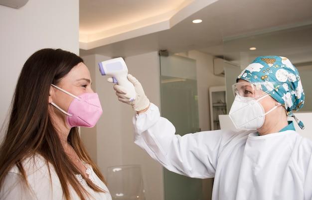 Verpleegster met persoonlijke beschermingsmiddelen, neemt de temperatuur met digitale thermometer naar de patiënt, tandheelkundige kliniek achtergrond
