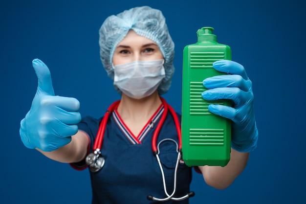 Verpleegster of arts met een fles omhoog ontsmettingsmiddel en duim.