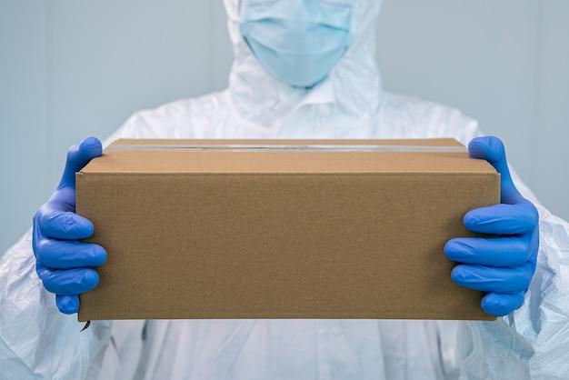 Verpleegster op beschermend pak toont een doos met beide handen in een ziekenhuis. de gezondheidswerker krijgt medische benodigdheden om coronavirus covid 19 te bestrijden. dokter met pbm, handschoenen en een chirurgisch masker