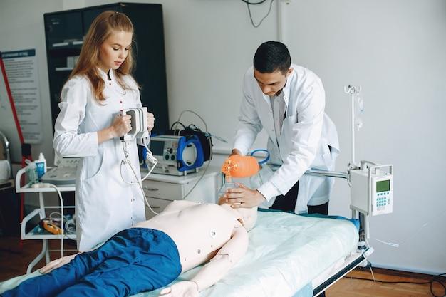 Verpleegster voert reanimatie uit. dokter helpt vrouw om de operatie uit te voeren. studenten oefenen geneeskunde uit.