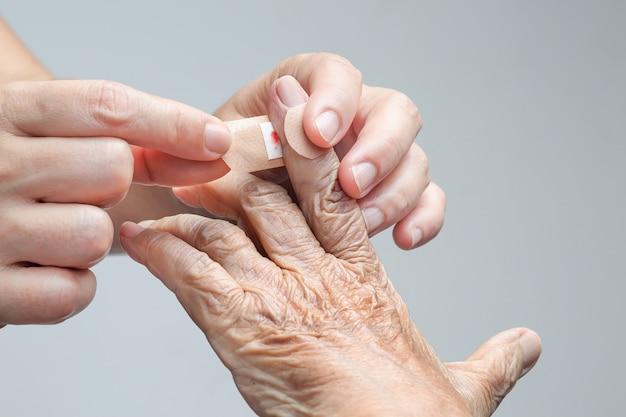 Verpleegster zelfklevend verband op de hand van de oudere vrouw