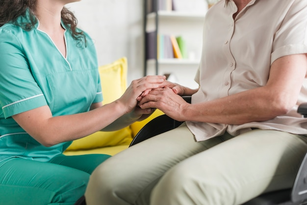 Verpleegsterholdingshanden van gehandicapte hogere vrouwenzitting op wielstoel