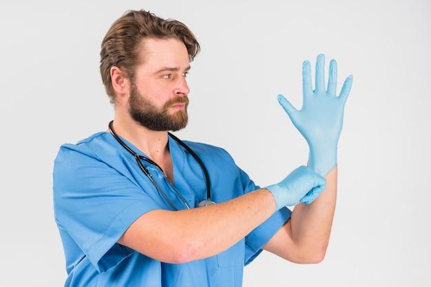 Verpleegstersmannetje met ernstig gezicht dat op handschoenen trekt