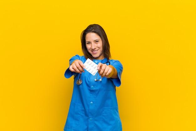 Verpleegstersvrouw met pils tegen oranje muur
