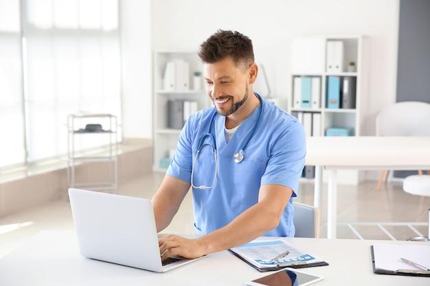 Verpleger die aan laptop in kliniek werkt