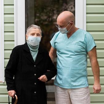Verpleger en hogere vrouw met stok bij verpleeghuis