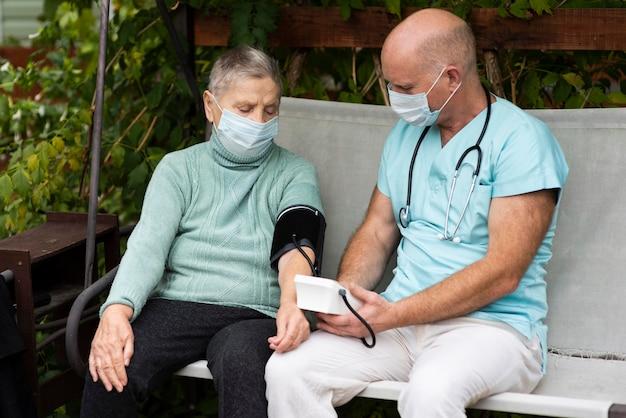 Verpleger met behulp van bloeddrukmeter op oudere vrouw