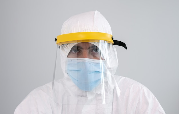 Verpleger op beschermend pak ppe en gezichtsmasker recht vooruit kijken. coronapandemie Premium Foto