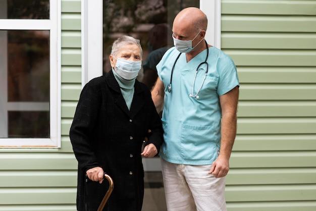 Verpleger poseren met oudere vrouw met stok