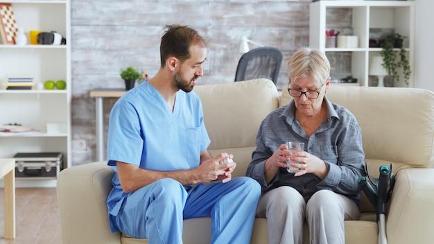 Verpleger zittend op de bank met senior vrouw die haar medische behandeling geeft in verpleeghuis.