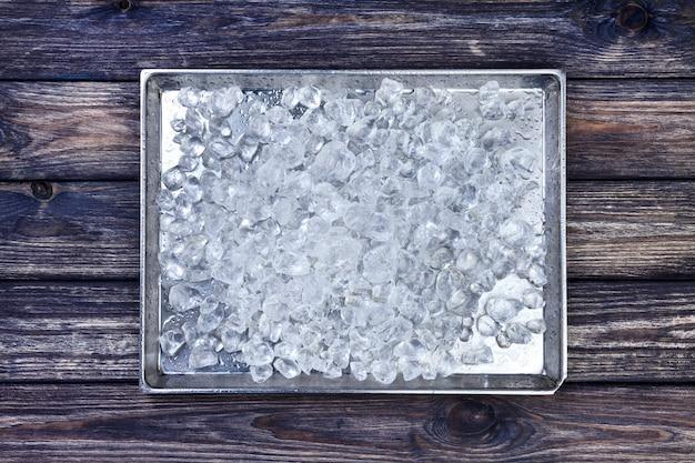 Verpletterd ijs op dienblad op hout. kopieer ruimte, bovenaanzicht