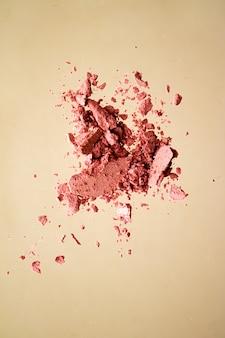Verpletterde cosmetica minerale organische oogschaduw blush en cosmetische poeder geïsoleerd op gouden achtergrond ...
