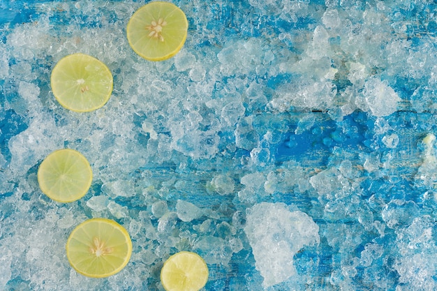 Verpletterde ijsblokjes en citroen, op vintage blauwe houten tafel. bovenaanzicht