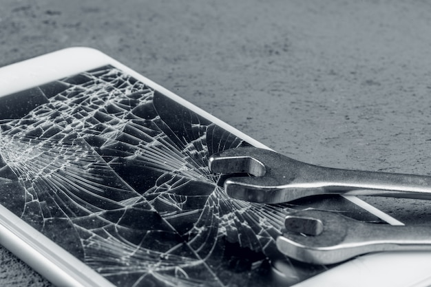 Verpletterde smartphone met het herstellen van hulpmiddelen op grijze muur
