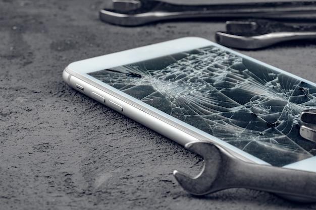 Verpletterde smartphone met reparatie tools op grijze achtergrond