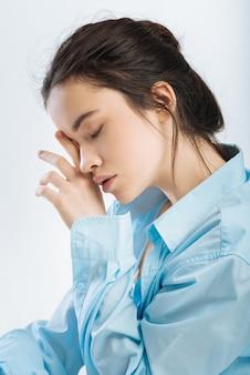 Verplicht dutje. melancholie aantrekkelijke jonge vrouw haar oog wrijven terwijl poseren in profiel en moet slapen