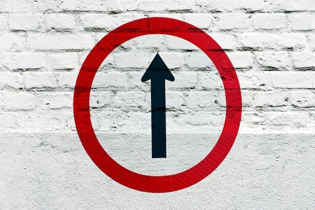 Verplichte richting: verkeersbord gestempeld op de witte muur, zoals graffiti