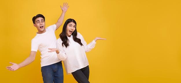 Verras jonge aziatische paar man en vrouw blij en verbaasd op panoramische gele achtergrond.