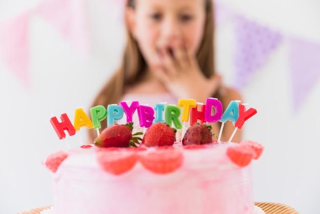 Verras leuk meisje achter de heerlijke cake van de aardbeiverjaardag