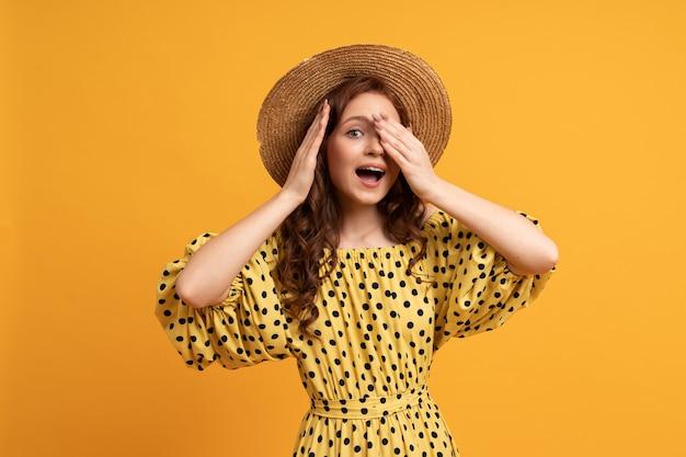 Verrassend gezicht. portret van rood hoofd vrouw in stro hoed poseren op geel in zomerjurk.