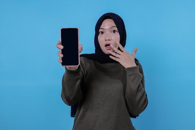 Verrassend jong aziatisch wijfje dat rode lange t-shirt draagt die mobiele telefoon houdt