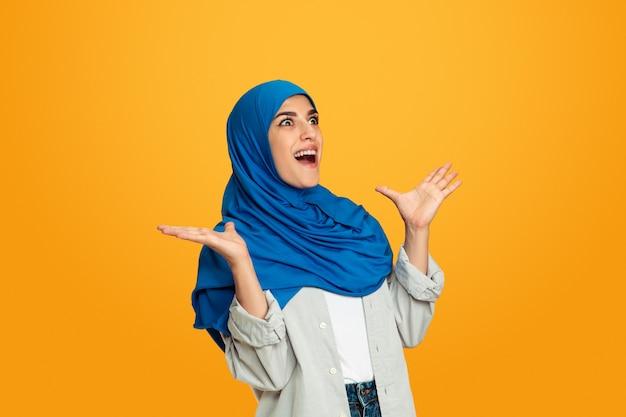 Verrassend. jonge moslimvrouw geïsoleerd op geel
