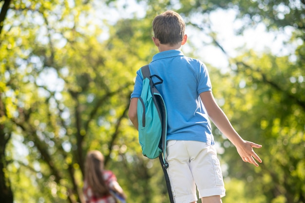 Verrassing, emotie. achteraanzicht van jongen in blauwe tshirt met rugzak op zijn schouder gebaren verrassing in park op zonnige dag